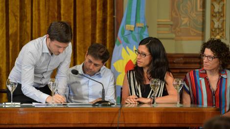 Costa firma ante la mirada de Kicillof y Paula Español.