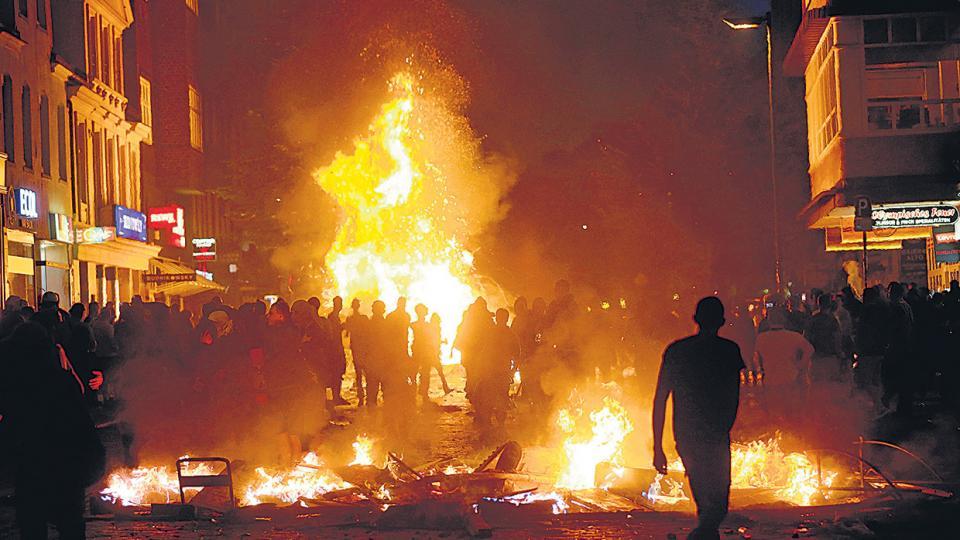 Manifestantes caminan entre barricadas incendiadas en el distrito de Schanzenvietel, de Hamburgo, Alemania.