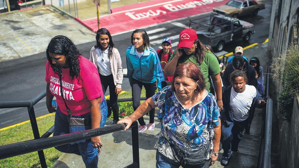 Mujeres venezolanas se dirigen a un centro de votación para elegir constituyentes en el emblemático barrio popular 23 de Enero de Caracas