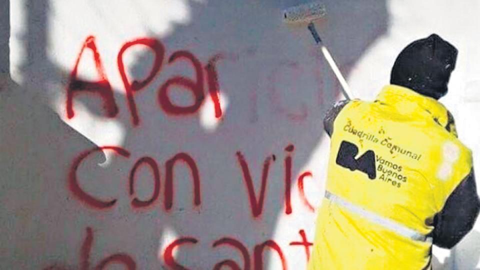 Un trabajador de la ciudad limpia pintadas que piden por la aparición de Santiago Maldonado.