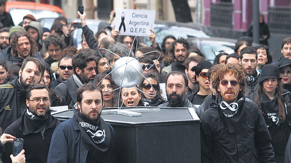 Becarios e investigadores hicieron una procesión vestidos de luto, frente al Polo Científico.