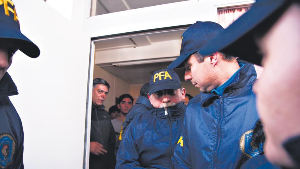 Uno de los gendarmes entra tapando su rostro al juzgado federal de Esquel.