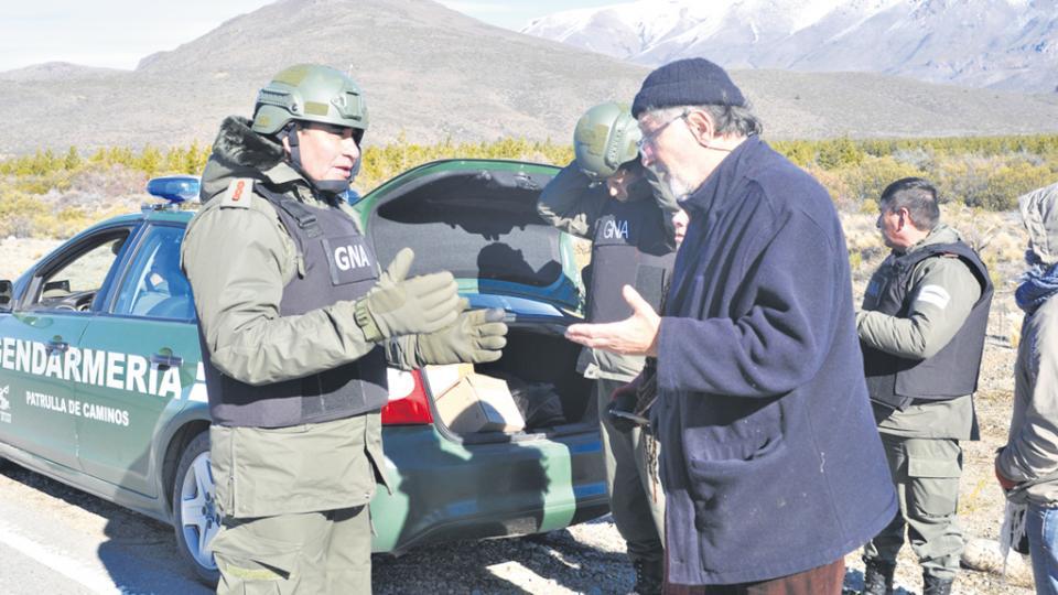 El civil, de lentes y gorro de lana, es Julio Saquero, interpelando a uno de los gendarmes desplegados en la zona.