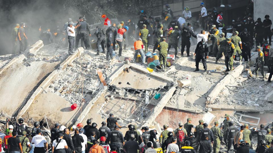 Los rescatistas, con picos, golpean sobre los bloques de hormigón para abrir vías de respiración e intentar localizar víctimas.