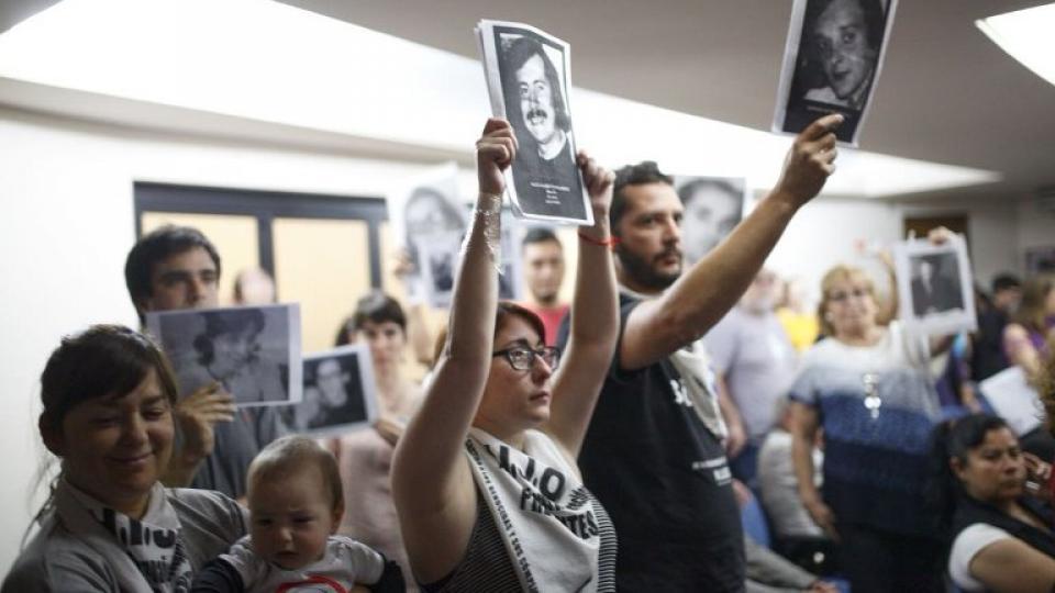 Los familiares muetran imágenes de las víctimas mientras se lee el fallo.