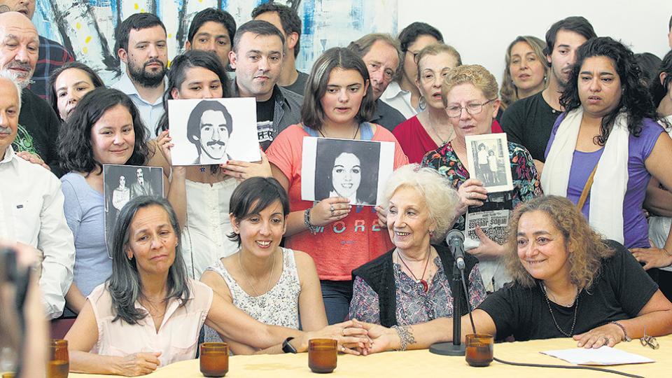 Adriana junto a Estela de Carlotto y sus tías Silvia y Marcela. Atrás, las fotos de sus padres.