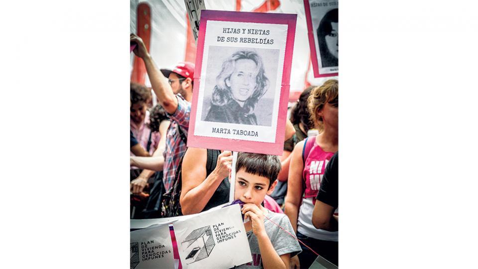 """En la columna de Ni Una Menos, un niño lleva la imagen de su abuela. En la pancarta, la leyenda """"Hijas y nietas de sus rebeldías""""."""