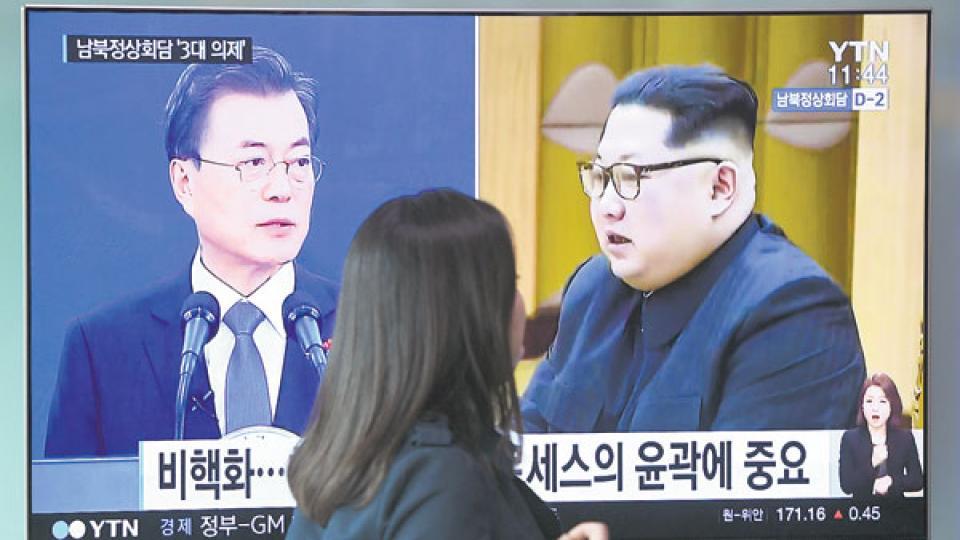 Moon y Kim aparecen en la pantalla de televisión ayer en una estación de subte de Seúl.
