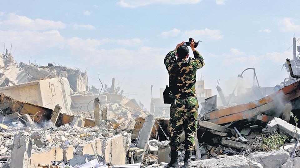 Un soldado sirio inspecciona las ruinas del edificio que era parte de un centro de investigación científica en Damasco.