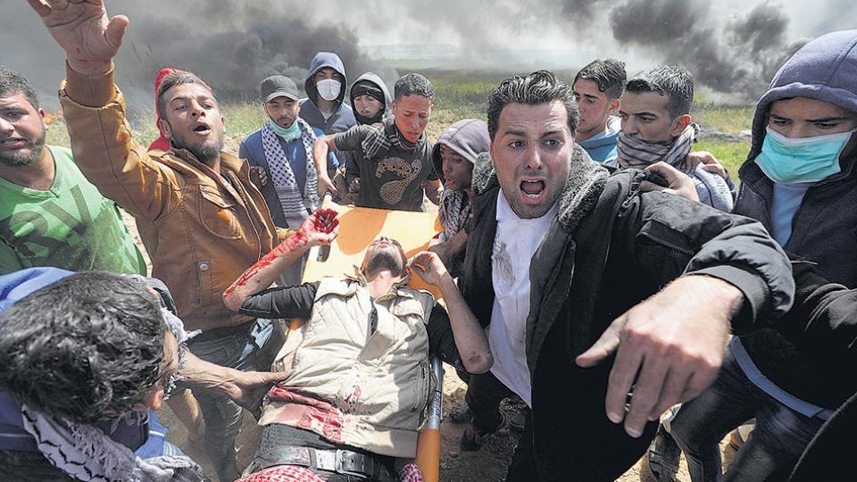 Manifestantes palestinos transportan en camilla a un activista herido en la frontera con la Franja de Gaza.