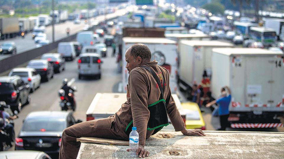Un camionero observa el bloqueo de una autopista en la entrada a Río de Janeiro, donde ya se siente el desabastecimiento de insumos básicos.