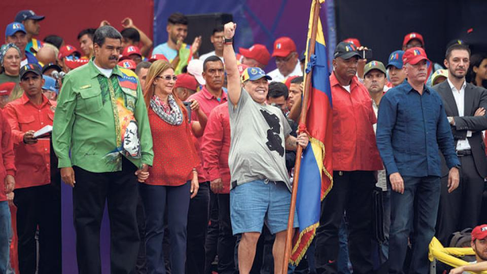 Maduro, de la mano de su esposa Cilia Flores, mira a Maradona, que saluda a la multitud puño en alto y bandera en mano durante el cierre de campaña.