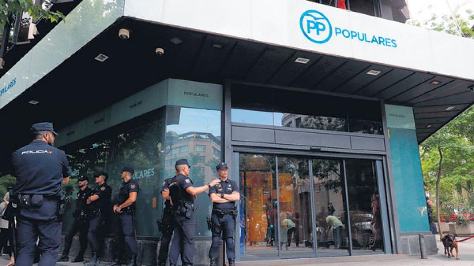 Policías custodian la sede del PP en Madrid tras el anuncio de la sentencia.