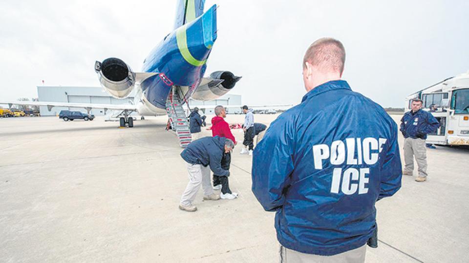 Un agente migratorio de EE.UU. controla mientras inmigrantes abordan un avión de la agencia para ser deportados.