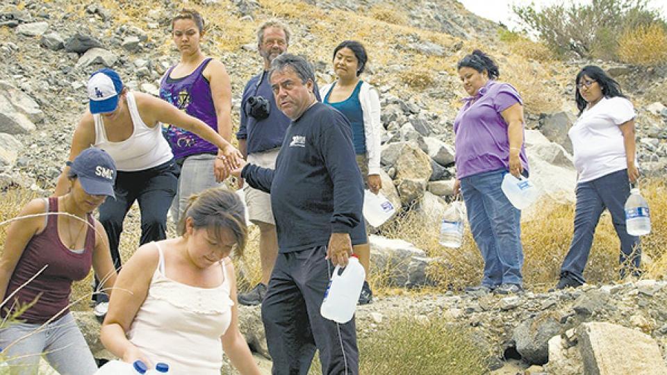 Morones (centro) ayuda a un grupo de inmigrantes a cruzar la frontera entre México y Estados Unidos.