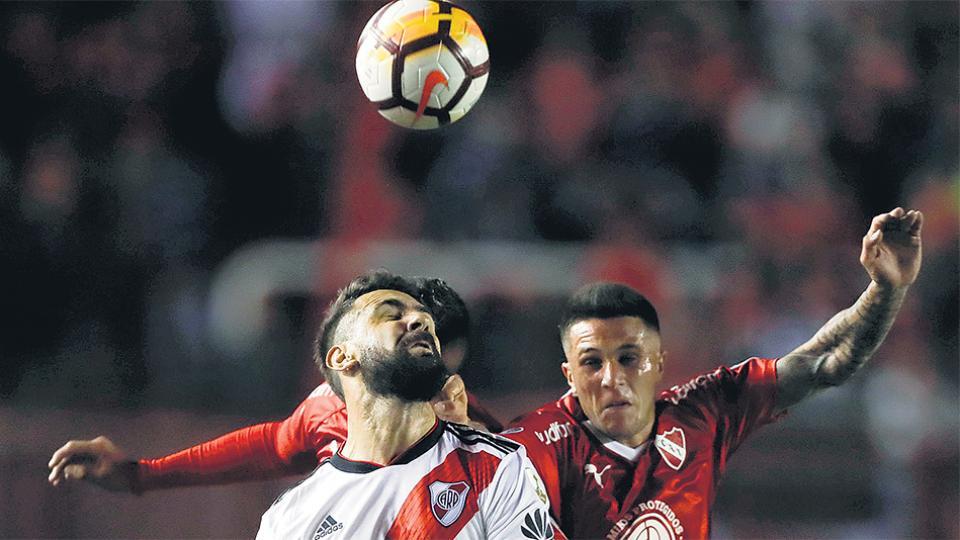 Pratto disputa la pelota con Bustos. Independiente y River igualaron sin tantos en Avellaneda.