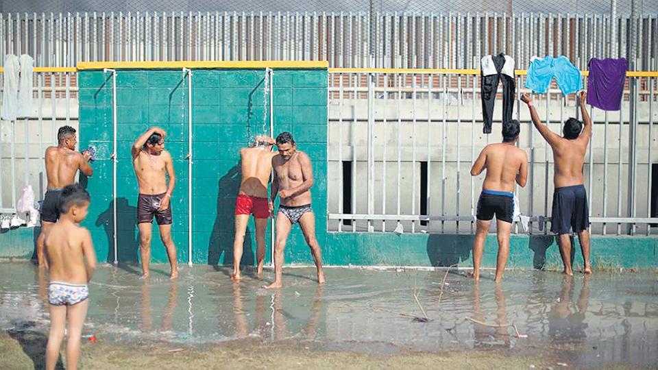 Cientos de inmigrantes centroamericanos se bañan en duchas en un improvisado campamento.