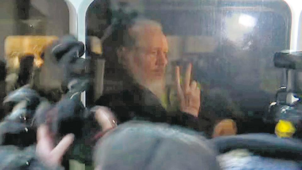 Assange saluda a sus seguidores camino al Departamento de Policía en Londres.