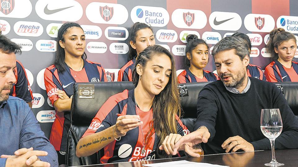 Macarena Sánchez firma su contrato junto al presidente Matías Lammens.