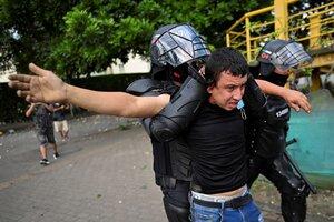 Policías colomianos detienen a un manifestante a la fuerza este viernes en Cali.