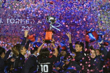 Medina, la capitana, levanta el trofeo. Y Sindy, la heroína, sonríe y la mira (Fuente: Prensa San Lorenzo)