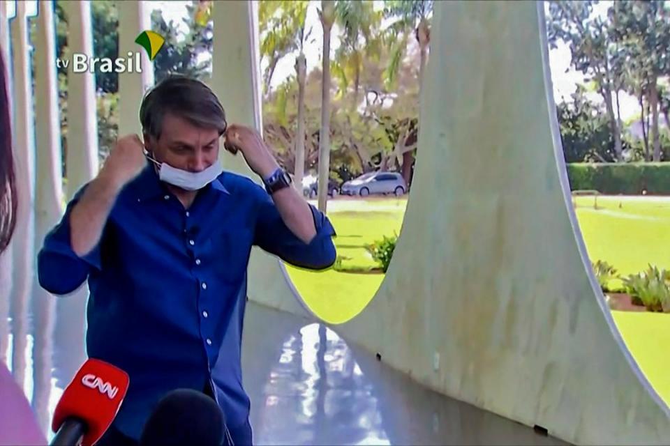 Captura de pantalla del momento en que Bolsonaro se saca el barbijo mintras informa que se contagió el virus.