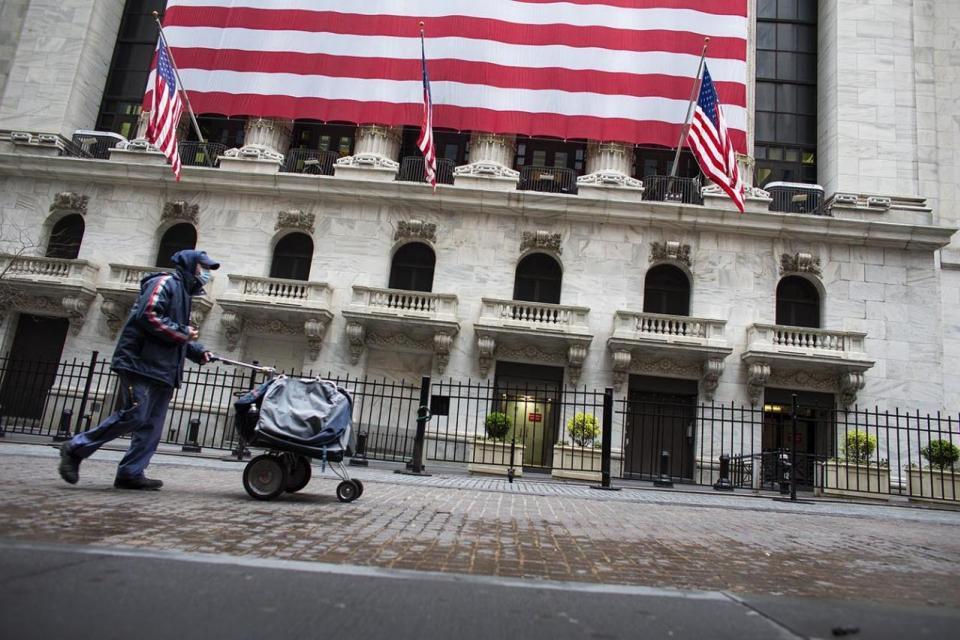 Un hombre empuja un carrito frente a la Bolsa de Comercio de Nueva York.
