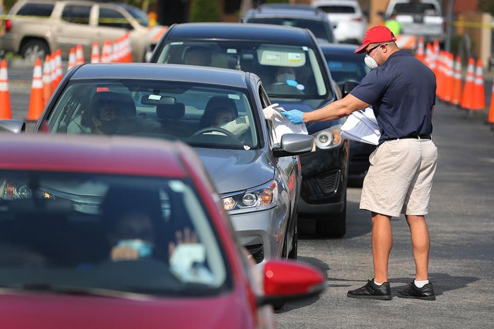 Reparto de formularios de desempleo frene a la biblioteca municipal en Hialeah, Florida.