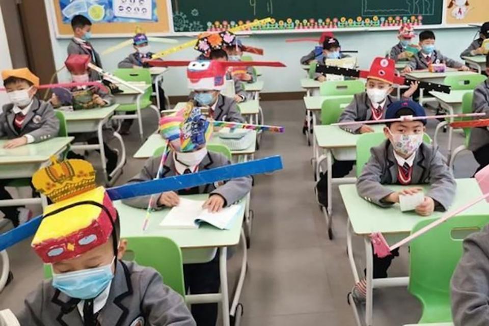 Una escuela de Zheijiang, China, donde los niños usan sombreros de cartón, con varillas a los costados para el distanciamiento.