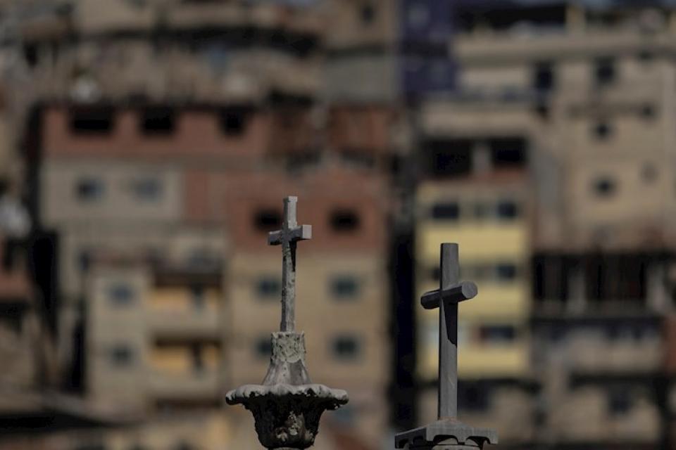Las cruces de tumbas en un cementerio, con una favela carioca de fondo.